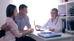 Healthy couple visiting doctor together, physician consults a young family about women fertility in medical office stock video