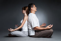 Healthy couple in yoga position on dark Stock Image