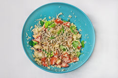 Healthy couscous salad in a blue bowl, top view. Healthy couscous, tomato, basil, cheese and sunflower seeds' salad in a blue bowl, close up view on a grey Stock Images
