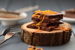 Healthy craft chocolate bars with orange rind on wood slabs. Closeup selective focus royalty free stock photos