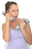 Healthy Crazy Fit Young Woman Using a Dumb Bell Weight as a Cell Phone Stock Images