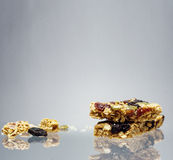 Healthy crunchy granola bar with reflection over gray background Royalty Free Stock Photos