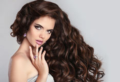 Healthy curly hair. Beautiful brunette woman model with makeup, Stock Images