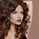 Healthy curly hair. Beauty Makeup. Brunette girl model with fash Stock Photography