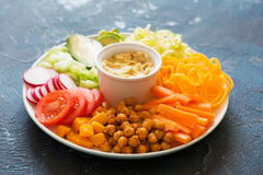 Healthy cut vegetables on the blue table. Rainbow vegan dinner plate, chickpeas and vegetables on the blue background Stock Photo