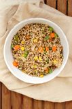 Healthy Czech vegan meal, buckwheat with carrot, sweet corn, peas, green beans and onion in white bowl with fork on the brown clot Stock Photos
