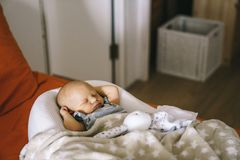 Healthy daytime sleep for the newborn. The baby is sleeping in the orthopedic Baby Cocoon on the bed in the room.  stock photography