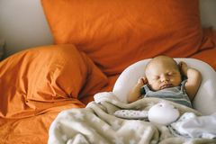 Healthy daytime sleep for the newborn. The baby is sleeping in the orthopedic Baby Cocoon on the bed.  royalty free stock images