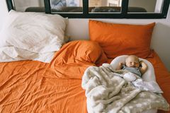 Healthy daytime sleep for the newborn. A child sleeps in the orthopedic Baby Cocoon on a larger bed in the parents room.  royalty free stock photography