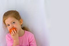 Healthy and delicious. Girl eating tomato Royalty Free Stock Images