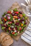 Healthy , delicious beetroot salad and goat cheese on variety of fresh mixed salad, garnished with pumpkin seeds and balsamic vine stock photography