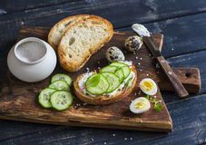 Healthy delicious breakfast or snack - open sandwich with goat's cheese and cucumber and boiled quail eggs. Royalty Free Stock Image