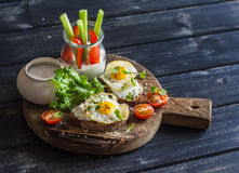 Healthy delicious breakfast or snack -  sandwich with cheese and a fried quail egg, greek yogurt, celery and sweet peppers Stock Photo