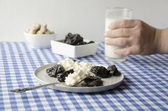 Healthy delicious breakfast time. Teenage hand taking glass of milk. Plate with cottage cheese, prunes, peanuts on table. Served t stock photo