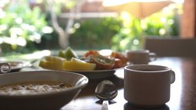 Healthy delicious breakfast with tropical fruit and oat porridge with cupof coffee on vacation time. Healthy delicious breakfast on vacation stock footage