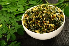 Bowl of moringa leaf curry- vegan diet food. Healthy delicious vegetarian dish made of moringa leaf and spices on a rustic background stock image