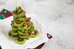 Healthy dessert idea for kids party - funny edible kiwi pomegranate Christmas tree Royalty Free Stock Image