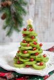 Healthy dessert idea for kids party - funny edible kiwi pomegranate Christmas tree Stock Photography