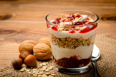 Healthy dessert with muesli, nuts and raspberry jam. Royalty Free Stock Photography