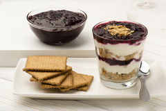 Healthy dessert with natural yogurt, full grain biscuits and black currant jam. Stock Photo