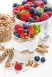 Healthy dessert with natural yogurt, muesli and berries. On a white background, vertical, closeup Stock Image