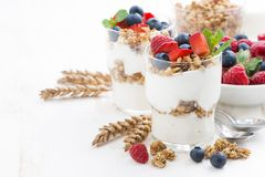 Healthy dessert with natural yogurt, muesli and berries. On white table, horizontal Stock Image