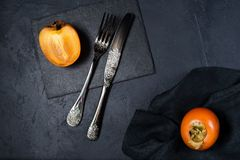Healthy dessert - persimmon on a black background. stock photo