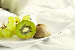 Healthy dessert served directly to bed. Green fruits on white background. Good diet Stock Image