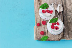 Healthy dessert. Dessert of yogurt and ripe raspberries on the blue old wooden table.health and diet food. copy space background for text Stock Image