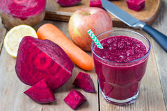 Healthy detox beetroot, carrot, apple and lemon juice smoothie in glass on a wooden table, horizontal Stock Photography
