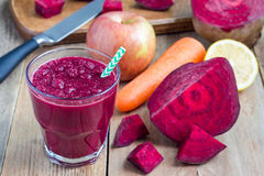 Healthy detox beetroot, carrot, apple and lemon juice smoothie, horizontal. Healthy detox beetroot, carrot, apple and lemon juice smoothie in glass on wooden Stock Image