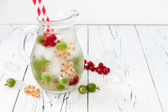Healthy detox berry infused flavored water. Summer refreshing homemade drink with gooseberries and white and red currant on white Royalty Free Stock Photo