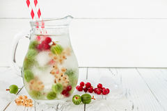 Healthy detox berry infused flavored water. Summer refreshing homemade drink with gooseberries and white and red currant on white Royalty Free Stock Images