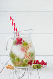 Healthy detox berry infused flavored water. Summer refreshing homemade drink with gooseberries and white and red currant on white Stock Photography