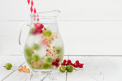 Healthy detox berry infused flavored water. Summer refreshing homemade drink with gooseberries and white and red currant on white Royalty Free Stock Image