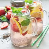 Healthy detox chia seed drink with strawberry, lemon and mint in glass jar, square format royalty free stock photography