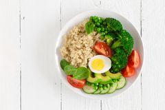 Healthy detox dish with egg, avocado, quinoa, spinach, fresh tomato, green peas and broccoli on white wooden background Stock Image