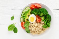 Healthy detox dish with egg, avocado, quinoa, spinach, fresh tomato, green peas and broccoli on white wooden background Stock Photo