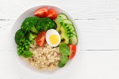 Healthy detox dish with egg, avocado, quinoa, spinach, fresh tomato, green peas and broccoli on white wooden background Stock Photography