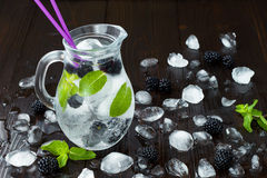Healthy detox flavored water with blackberry and mint. Cold refreshing berry drink with ice on dark wooden table. Copy space backg Stock Images