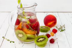 Healthy detox fruit infused flavored water. Summer refreshing homemade cocktail with fruits, thyme on wooden table. Clean eating stock photo