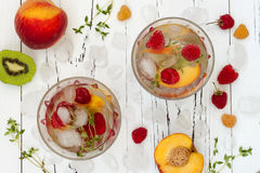 Healthy detox fruit infused flavored water. Summer refreshing homemade cocktail with fruits, thyme on wooden table. Clean eating Royalty Free Stock Images