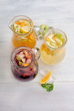 Healthy detox fruit lemonade. Healthy detox fruit infused flavored water. Summer refreshing homemade cocktail with fruits on white wooden table top view Royalty Free Stock Images