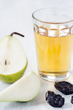 Healthy detox meal of apple juice, pear and prunes. Glass of apple juice with pear and dried prunes for a healthy detox meal to aid digestion Stock Photos