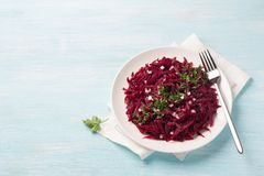 Healthy detox raw beetroot salad with red onion, garlic, herbs and spices. On a blue background. diet food. top view, free space Royalty Free Stock Photography