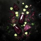 Healthy detox smoothies or juice from red cabbage, cucumbers with chia seeds in glass bottles on gray kitchen table background,. Vegan fitness drink concept stock photo