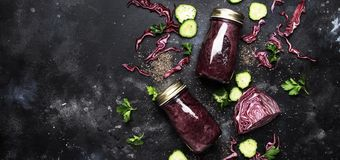 Healthy detox smoothies or juice from red cabbage, cucumbers with chia seeds in glass bottles on gray kitchen table background,. Vegan fitness drink concept royalty free stock photography