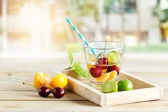 Healthy detox water, glass of cherry, orange and lime on wooden tray Stock Images