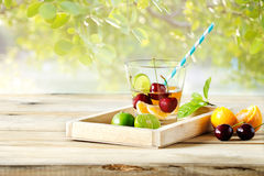 Healthy detox water, glass of cherry, orange and lime on wooden tray Royalty Free Stock Photos