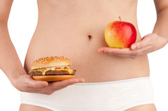 Healthy diet 01. A young woman choosing an apple over a hamburger stock photography